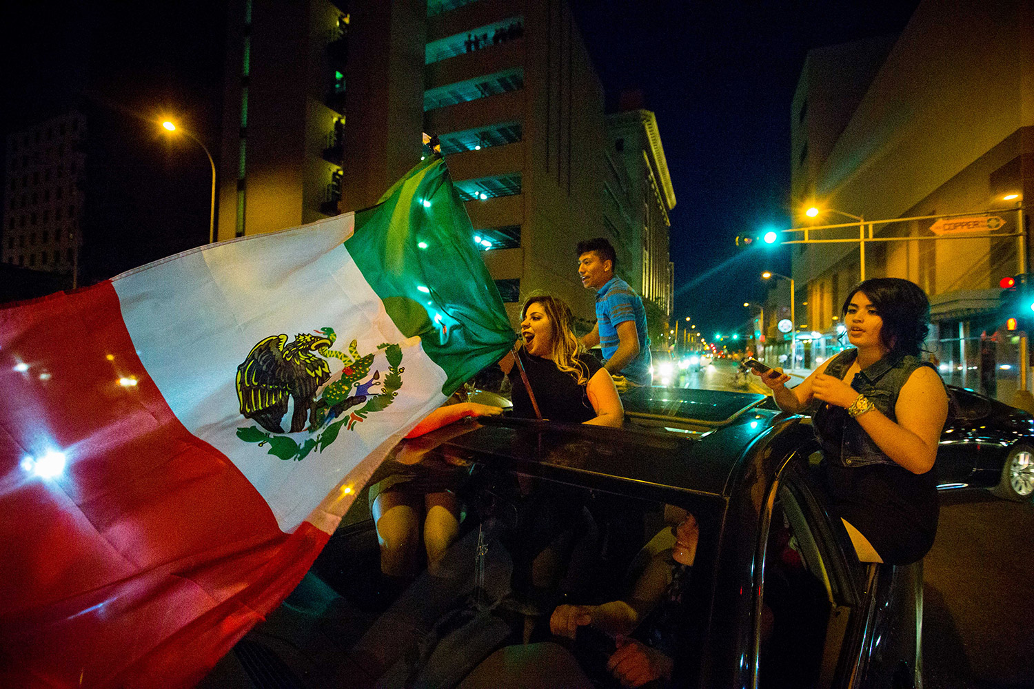 A woman waves the Mexican flag while driving past the Albuquerque Convention Center after a rally by Republican presidential candidate Donald Trump.