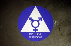 A new sticker designates a gender neutral bathroom at Nathan Hale high school Tuesday in Seattle.  Nearly half of the district's 15 high schools already have gender neutral bathrooms and one high school has had a transgender bathroom for 20 years.