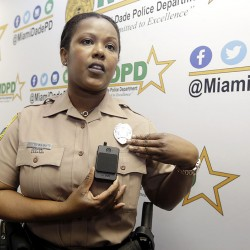 Marjorie Eloi, public information officer for the Miami-Dade Police Department, shows how to turn on a body camera, which the department will assign to about 1,000 officers in the next few months. The Associated Press