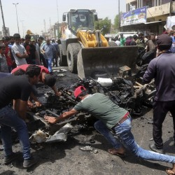Civilians help a municipality bulldozer clean up at the scene of a car bomb explosion at a crowded outdoor market in the Iraqi capital's eastern district of Sadr City Wednesday. The Associated Press