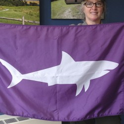 Leslie Reynolds, chief ranger at the Cape Cod National Seashore, displays a shark-alert flag at the U.S. Parks Service's Cape Cod headquarters in Wellfleet, Mass.