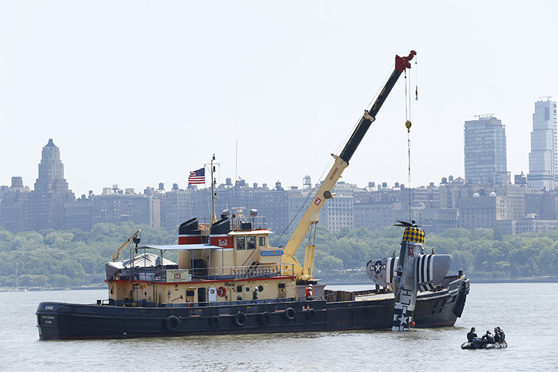 Officials remove the World War II vintage P-47 Thunderbolt out of the Hudson River a day after it crashed.