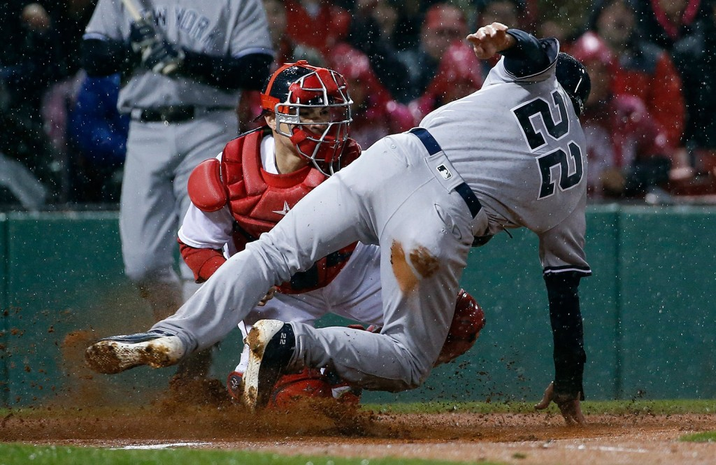 Boston's Christian Vazquez, behind, makes the tag on New York's Jacoby Ellsbury (22) at home plate on a fielders choice.