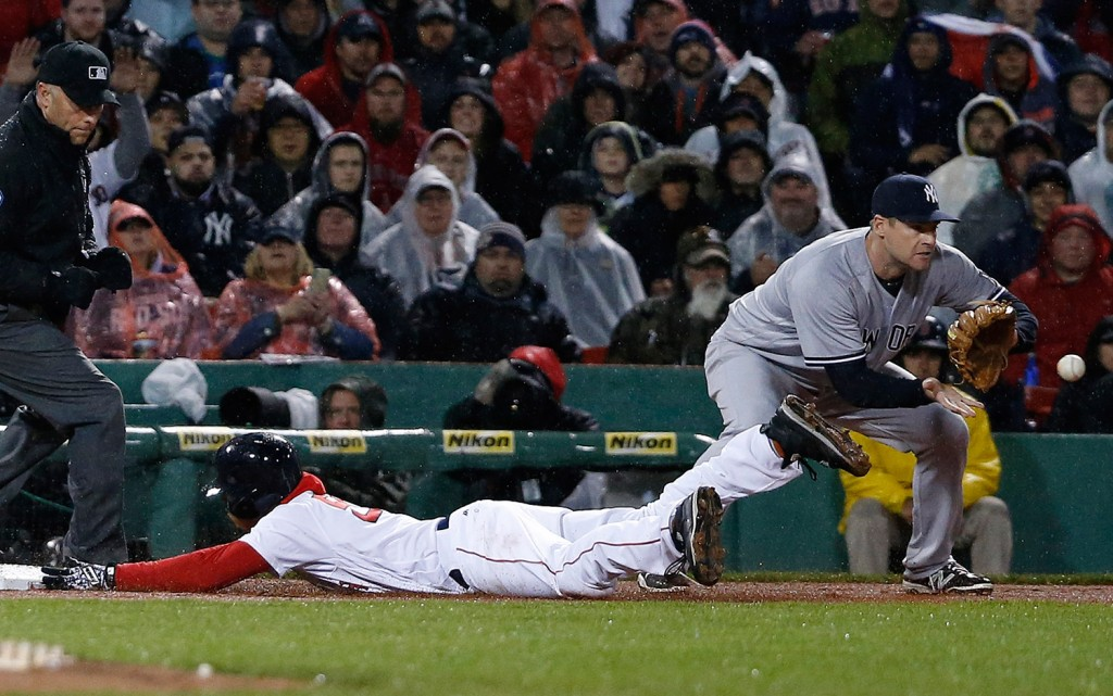Mookie Betts slides safely into third base as New York's Chase Headley, right, gets the throw on a single by Dustin Pedroia.