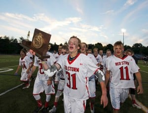 Scarborough's Cameron Nigro carries the Class A boys' lacrosse state championship trophy to show the Red Storm fans at Fitzpatrick Stadium. Scarborough defeated Brunswick to claim the title.