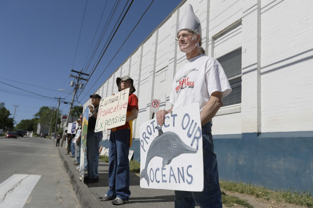 Russell Wray, of Hancock, wears a homemade dolphin hat as he protests outside of Bath Iron Works before the start of the christening ceremony for the USS Michael Monsoor .