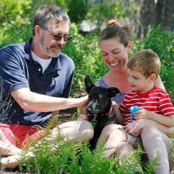 Idexx employee Jon Lawpaugh, his wife, Jen, and their son Emrys, 3, sit with their newly-adopted dog, Sampson, before taking him home for the first time.