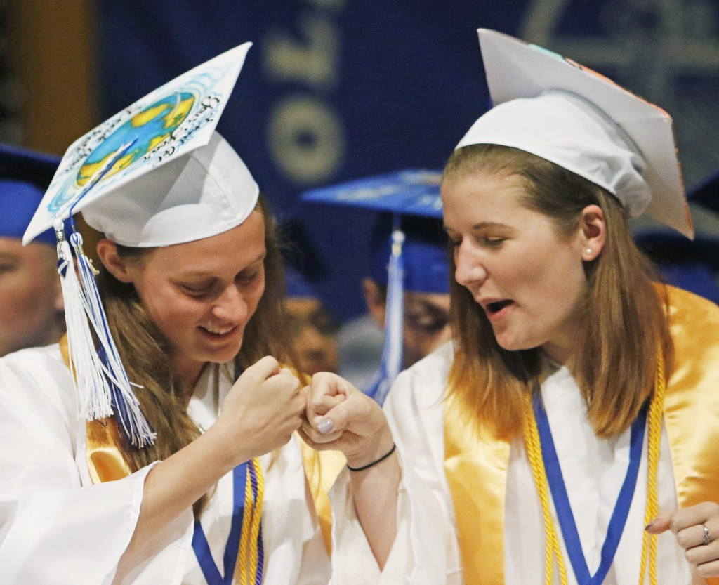 OLD ORCHARD BEACH, ME - JUNE 5: Jenny Cobb, left, and Mariah Bouthiller fist bumb during scholarship announcements at Old Orchard Beach High School graduation. (Photo by Jill Brady/Staff Photographer)