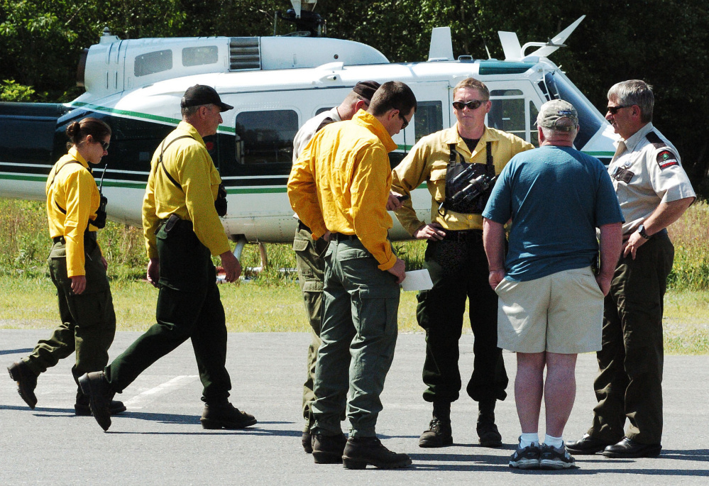 Maine Forest Service personnel consult on Monday at the Kingfield Fire Department on status of the fire at the summit of nearby Mount Abram with incident commander Maine Forest Ranger Shane Nichols, third from right, and Chief Ranger William Hamilton.
