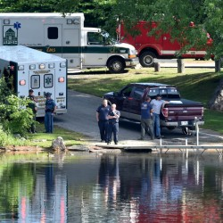 Paramedics from Reddinton Fairview General Hospital, state police troopers and wardens from the Maine Warden Service stand by the dock Thursday at the Oosoola Park boat landing as a crew searches for an apparent drowning victim in the Kennebec River in Norridgewock.