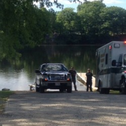 Two emergency responders wait by the Kennebec River late Thursday afternoon where searchers in the river were looking for someone in a boat — possibly a child — who had gone overboard.