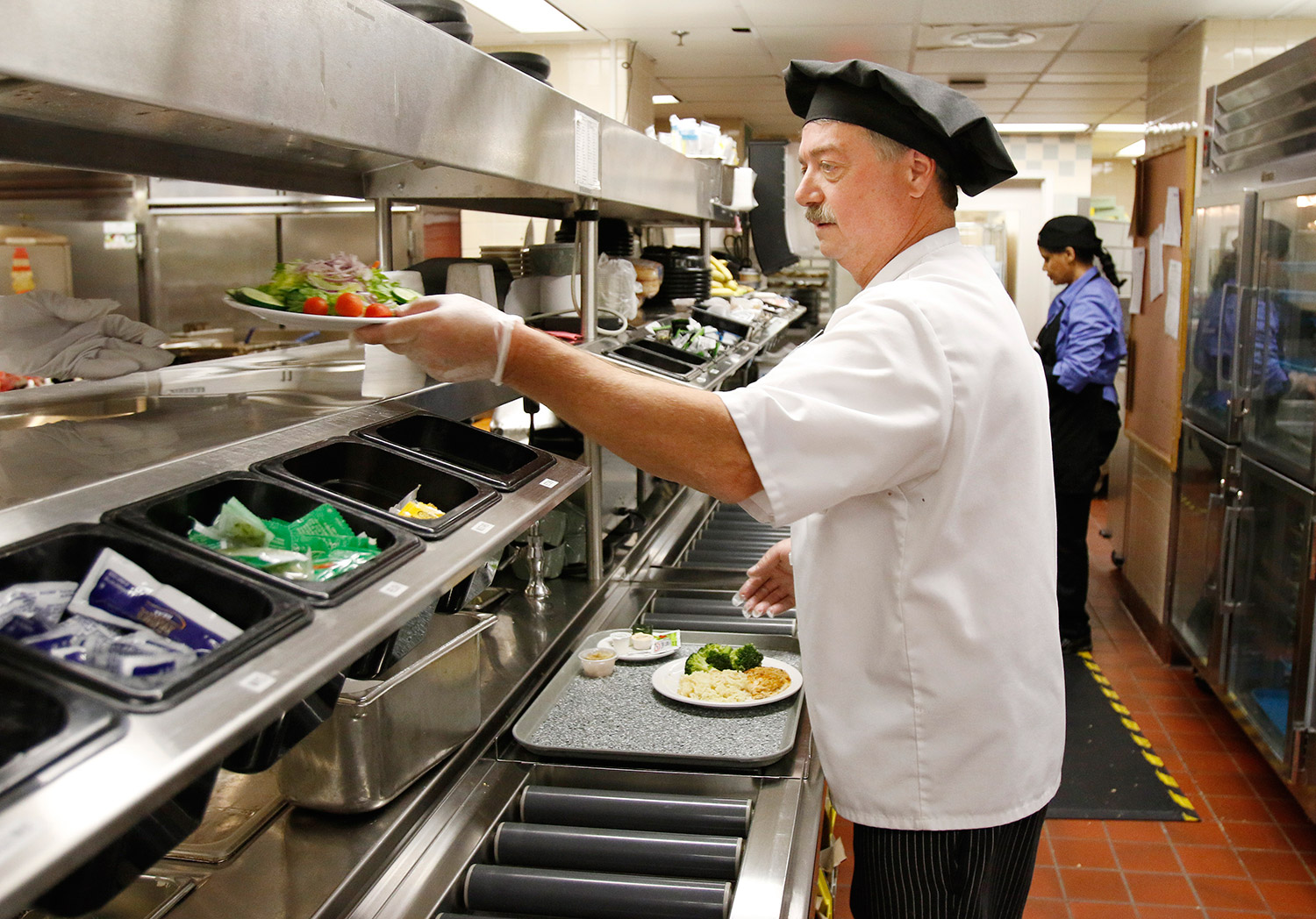 Danny Cummings, production manager and chef at Maine Medical Center, assembles a tray of food at the Portland hospital.