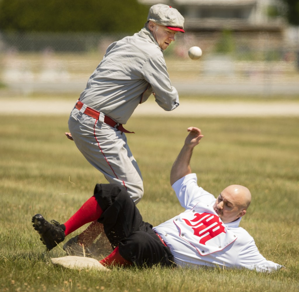 CORNISH, ME - JUNE 25: Flemington (New Jersey) Neshanock third baseman Joe Murray misses the throw as North Andover (MASS) MechanicÕs baserunner Brett Zani slides safely into the base during the New England Vintage Base Ball Festival at the Cornish Fairgrounds in Cornish, Maine on Saturday, June 25, 2016. A benefit in helping to restore and preserve the Cornish Fairgrounds, organised by the townÕs historical society and fairground committee, the festival will continue on Sunday with more 1864-rules baseball featuring six vintage base ball clubs from Maine, New England and New Jersey. Some of the rules in place during that era that are different than todayÕs game, include a player is ruled out if the ball is caught by the first hop, a ball that first lands in play that goes foul is considered a fair ball and pitches are made underhand. (Photo by Carl D. Walsh/Staff Photographer)