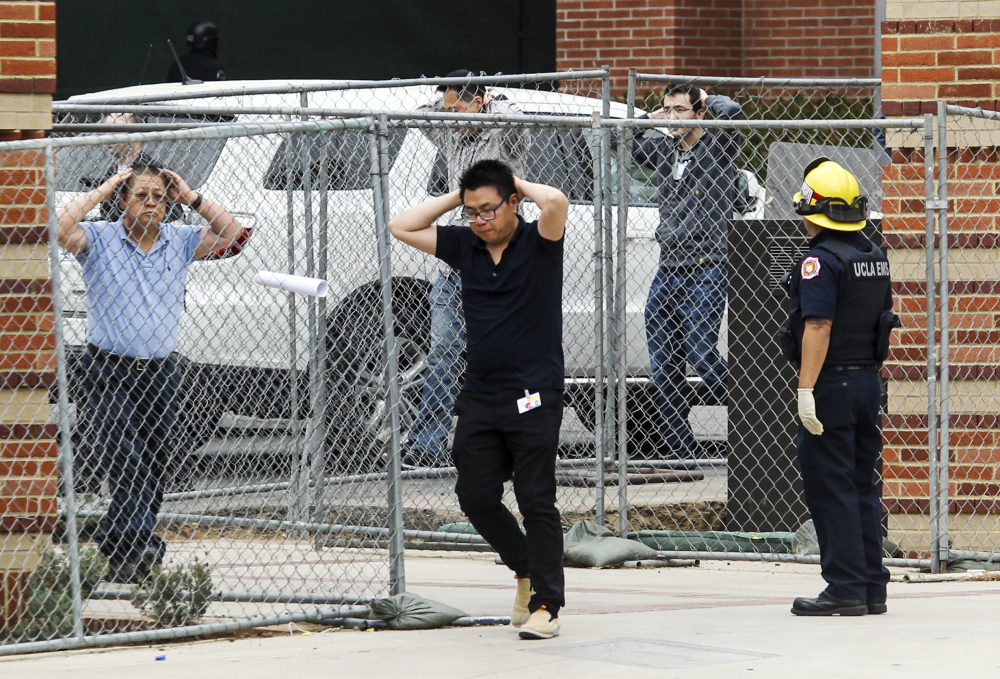 People are escorted by emergency personnel away from the scene of Wednesday's murder-suicide at the University of California Los Angeles.