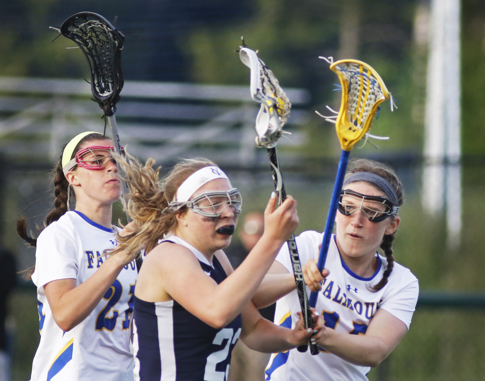 Yarmouth's Meredith Lane pushes forward past pressure of Falmouth's, left, Sydney Bell and Gabby Farrell in first half of Wednesday's girls' lacrosse game. Falmouth won, 14-7.