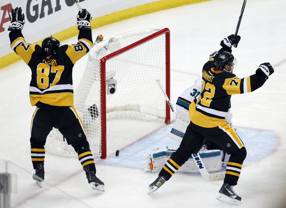 Sidney Crosby and Patric Hornqvist, right, of the Penguins celebrate a goal by Conor Sheary against Sharks goalie Martin Jones in overtime in Game 2 of the Stanley Cup Final Wednesday in Pittsburgh. The Penguins won 2-1 to take a 2-0 lead in the series.