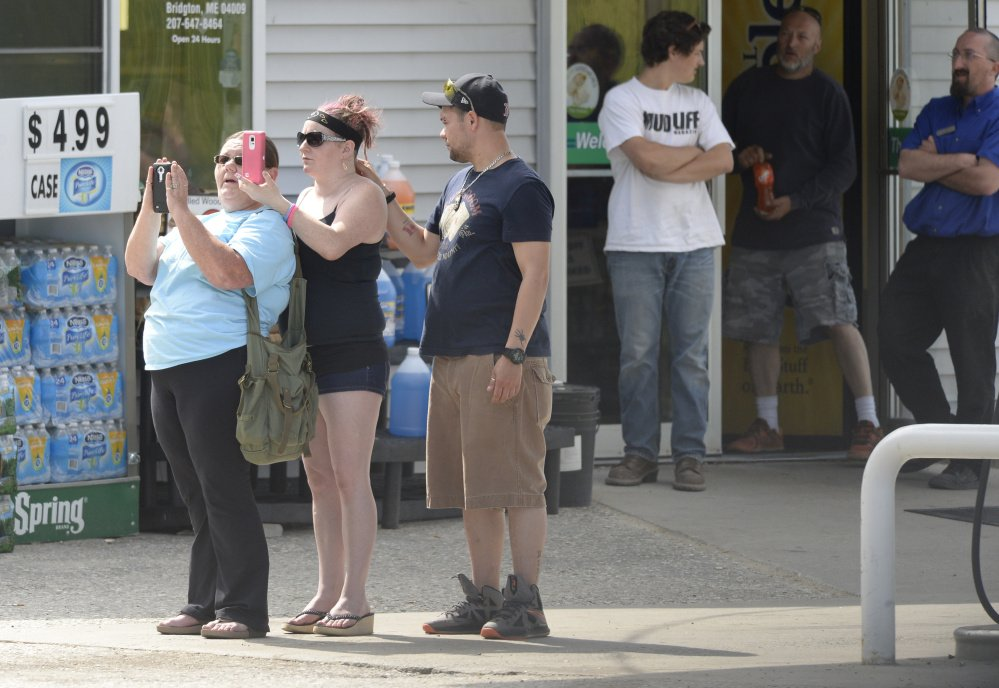 At a nearby gas station, people record videos and watch as the situation unfolds at the First and Last Motel in Bridgton on Thursday.