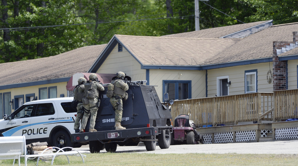 A tactical team from the Cumberland County Sheriff's Office takes position at the First and Last Motel in Bridgton during Thursday's standoff. Shawn Patrick Ouellette/Staff Photographer