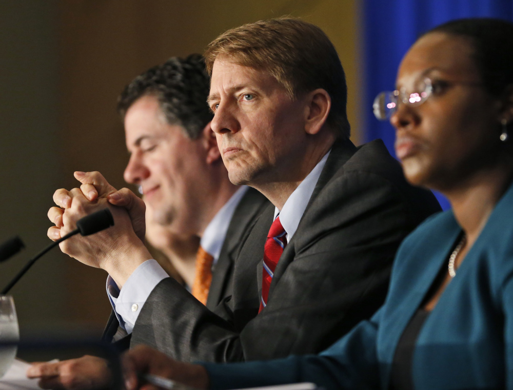 "Consumer Financial Protection Bureau Director Richard Cordray, center, says, ""Too many borrowers seeking a short-term cash fix ... sink into long-term debt."""