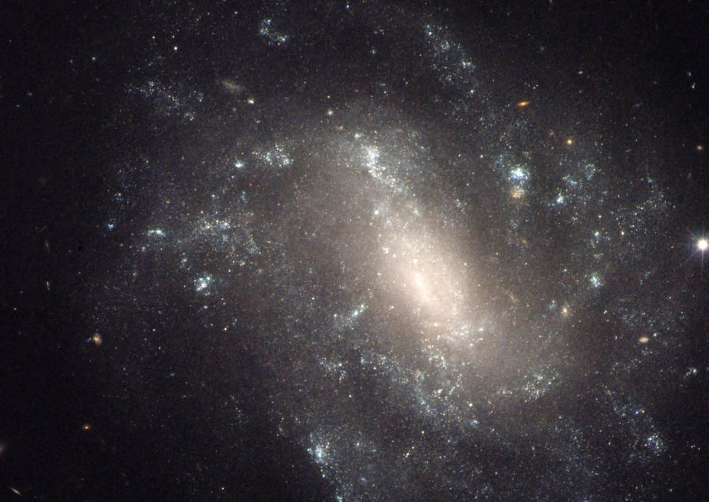 NASA image shows a barred spiral galaxy 130 million light-years away, one of the measurements that astronomers used to come up with a faster rate of expansion of the universe.