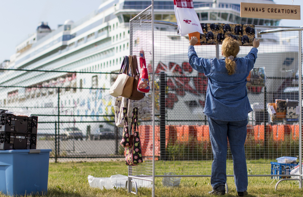 Joyce Whittemore of Carthage drapes some of the clothing and handbags she sells from her booth along the waterfront Thursday, with the Norwegian Gem looming in the distance. A city policy that took effect Wednesday restricts where street vendors can set up when cruise ships carrying more than 1,000 passengers visit Portland.