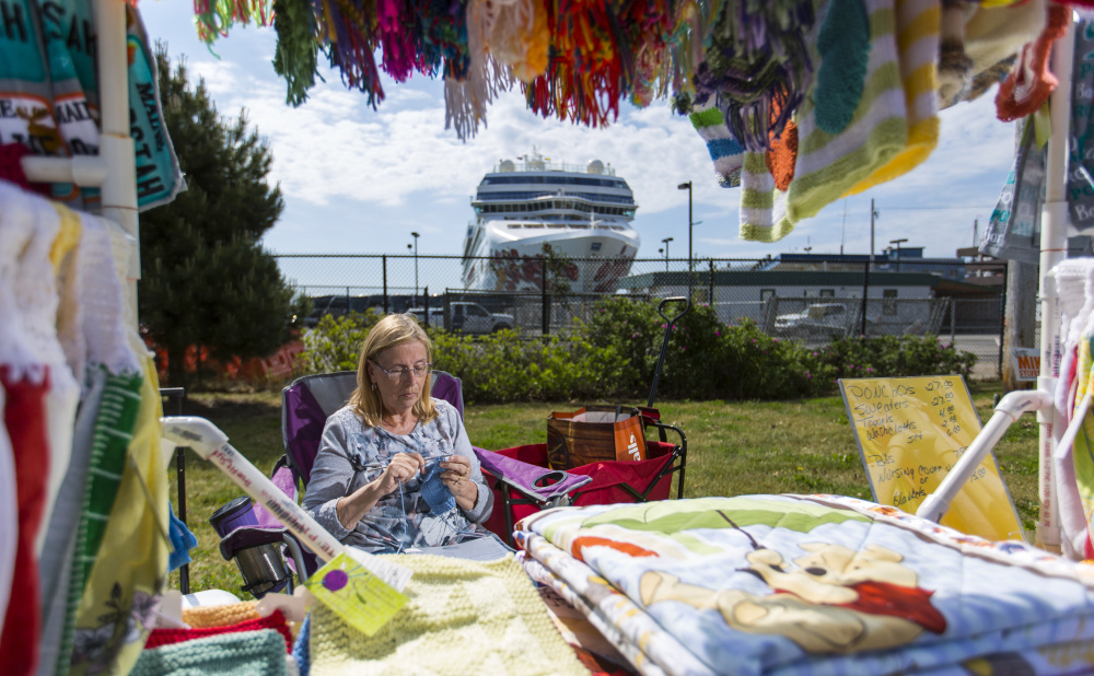 With the Norwegian Gem docked at the Portland Ocean Terminal behind her, Donna Pradon of Wells sells hand-knit quilts and blankets Thursday. She and other street vendors say foot traffic is directed away from where they are now required to set up their booths.