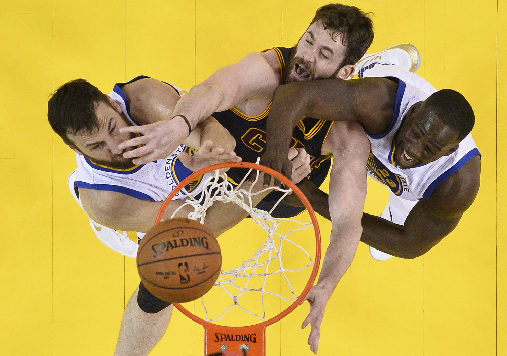 Cleveland forward Kevin Love, center, reaches for the ball between Golden State center Andrew Bogut, left, and forward Draymond Green in the first half of Thursday night's game in Oakland.