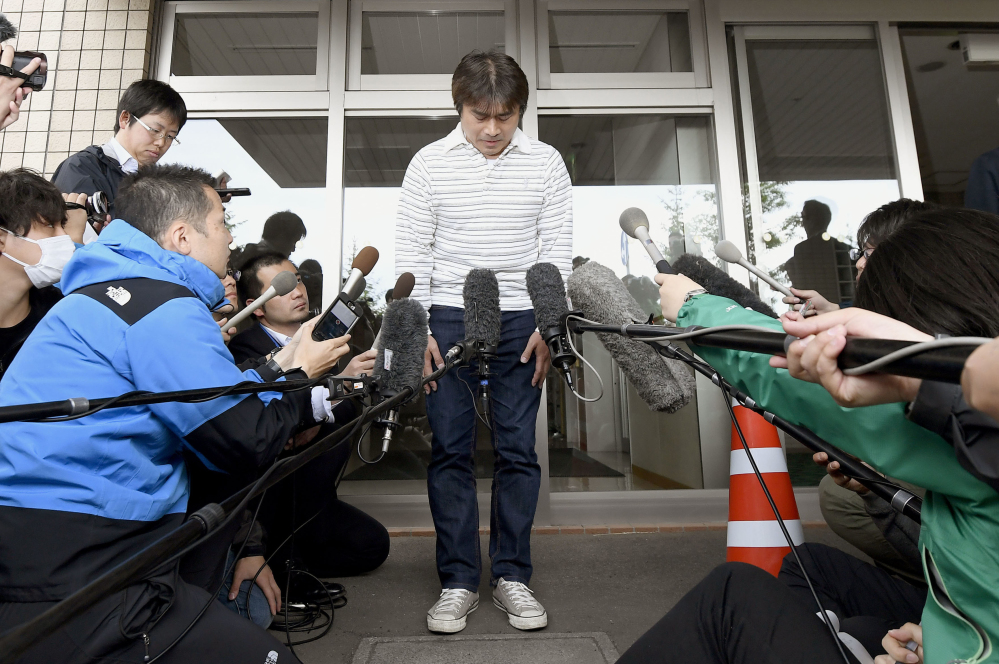 Takayuki Tanooka, father of the 7-year-old Japanese boy who went missing nearly a week ago, bows in front of media after his son was found, in Hakodate, Hokkaido, on Friday.
