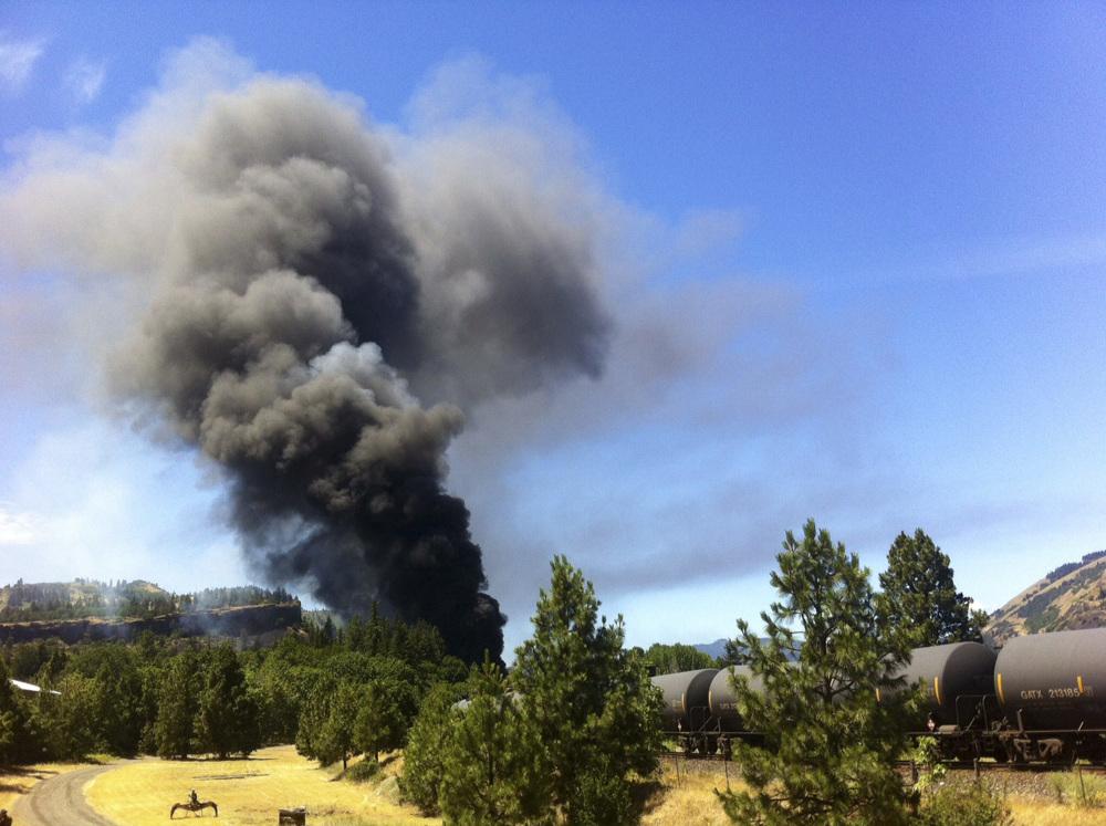 A train towing cars full of oil sends up a plume of smoke after derailing Friday near Mosier, Ore., near the scenic Columbia River Gorge. The accident happened just after noon about 70 miles east of Portland.