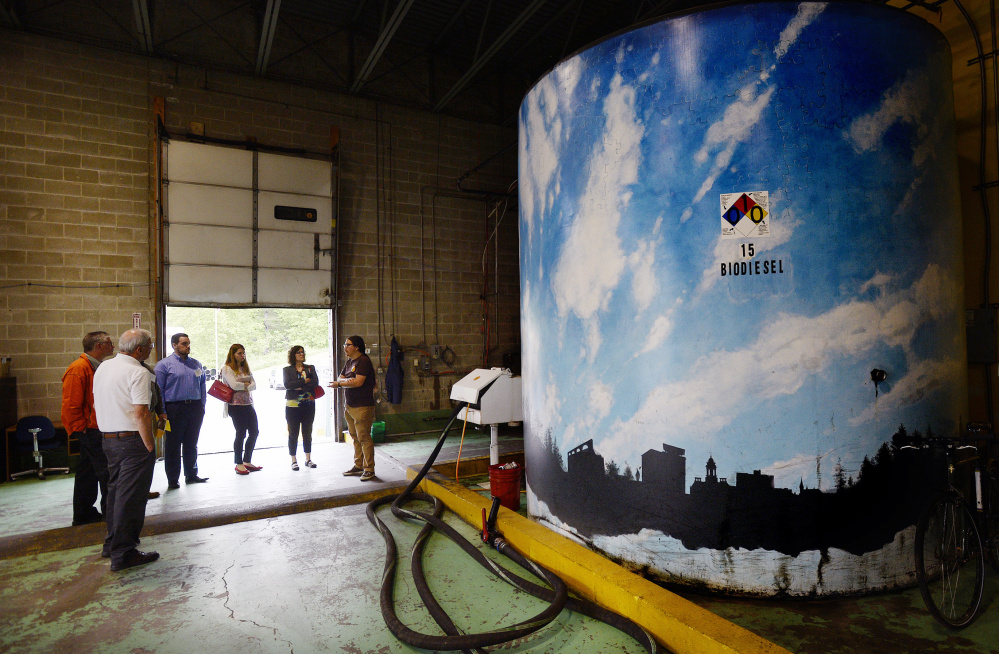 Alex Pike, right, of Maine Standard Biofuels leads a tour of the plant Friday during the Plants to Products Forum. To the right is a tank with the company's finished product, biodiesel.