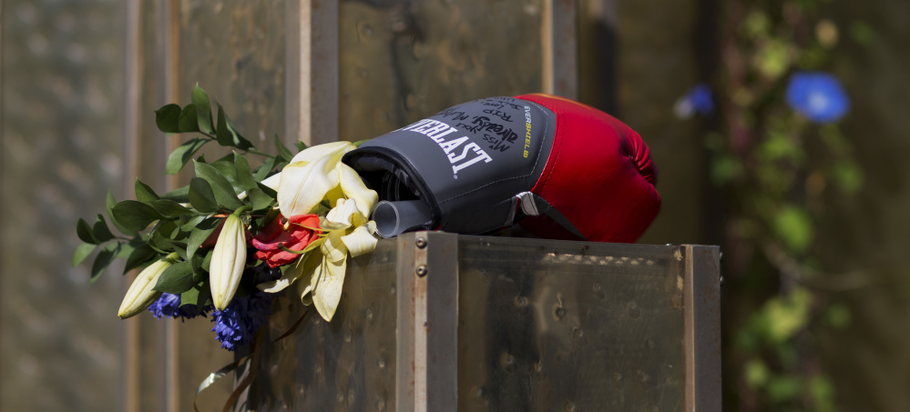 Flowers and a boxing glove are left at a makeshift memorial to Muhammad Ali at the Muhammad Ali Center. Ali's memorial service will feature former President Bill Clinton.