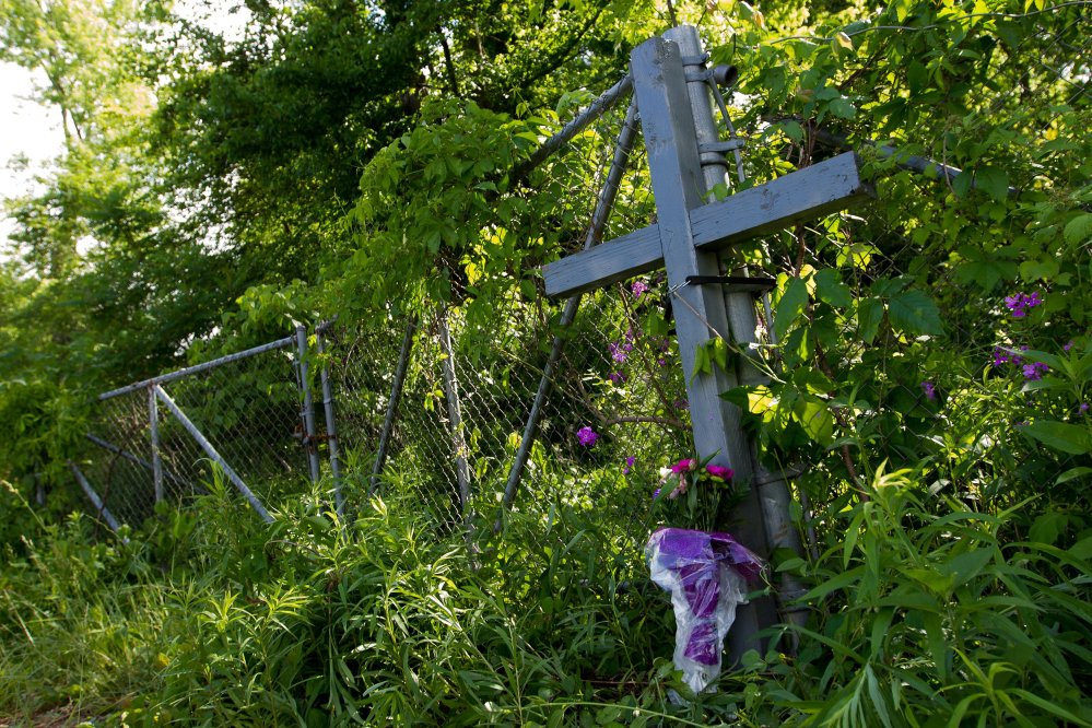A cross and flowers form a memorial at the scene of Tuesday's fatal crash in Cooper Township, Mich.