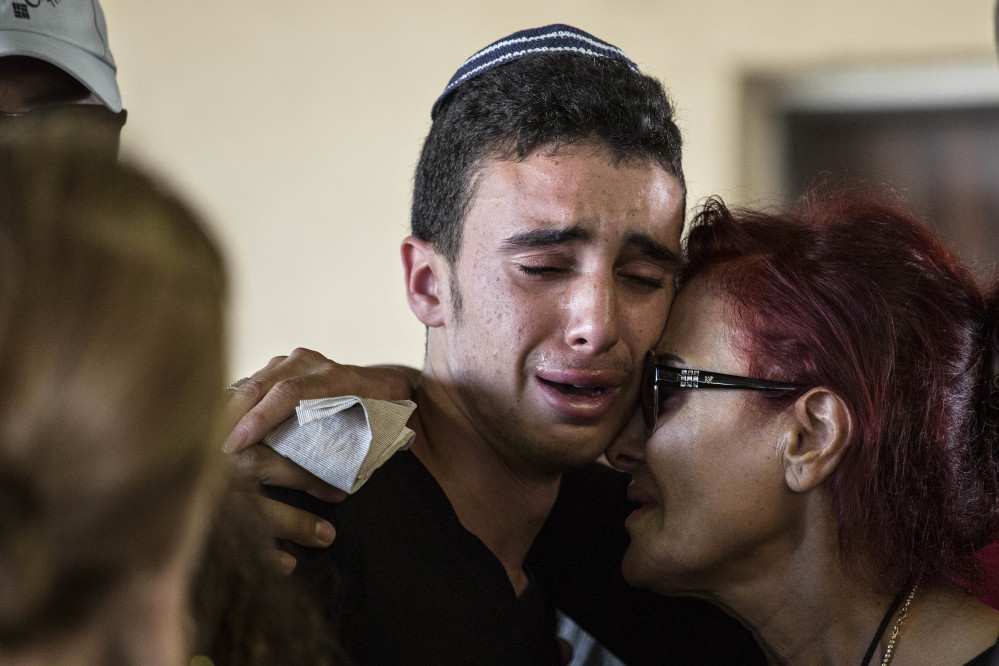 Israeli relatives mourn during the funeral of Ido Ben Arieh, 42, at the cemetery in Yavne, Israel, on Thursday. A shooting by two West Bank Palestinians killed four people.