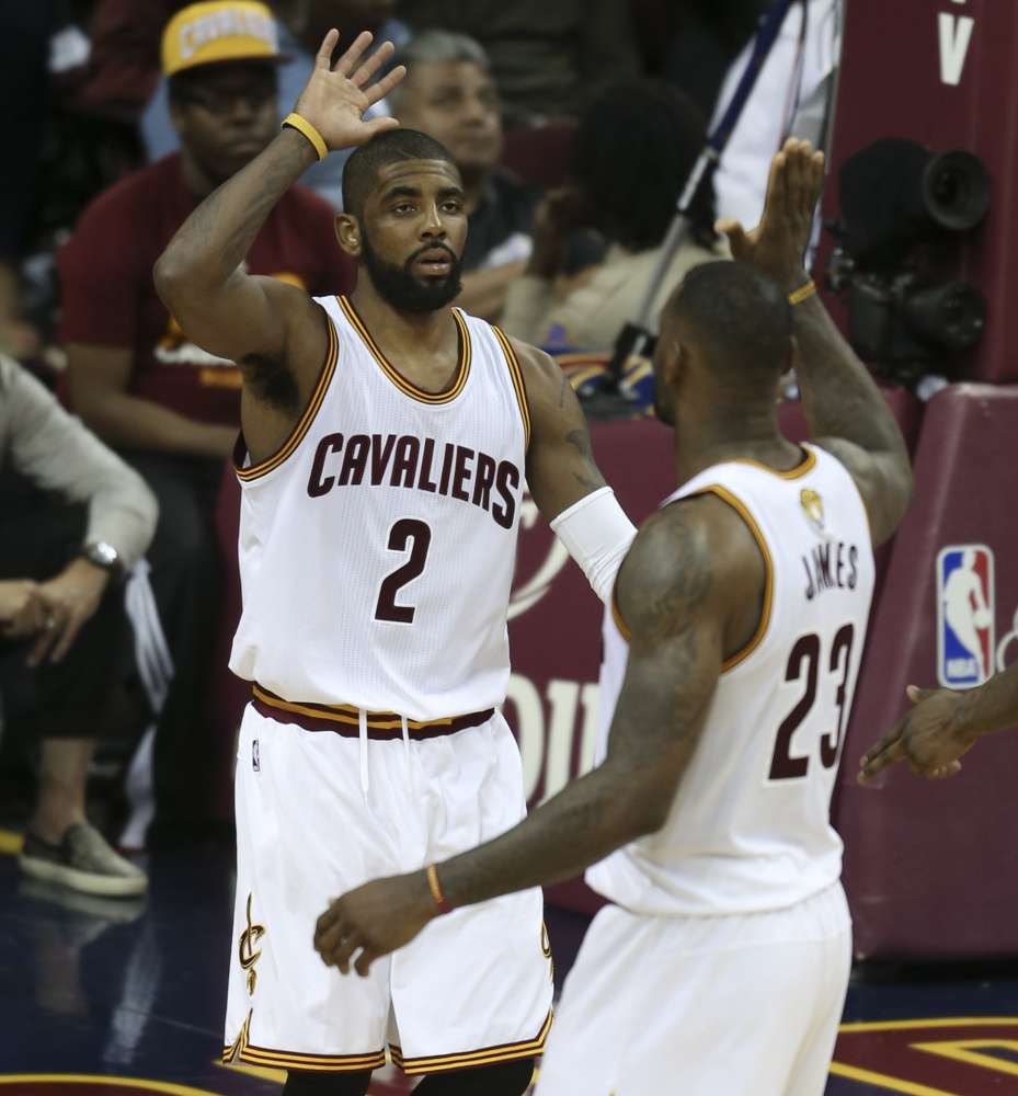 Kyrie Irving, left, and LeBron James of the Cavaliers celebrate their 120-90 win against the Warriors in Game 3 of the NBA Finals on Wednesday. The two stars promised to pick up the slack for ailing teammate Kevin Love, out with a concussion.