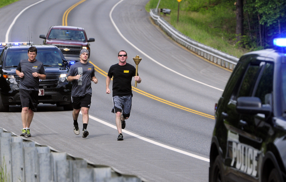 Monmouth Police Chief Kevin Mulherin, left, Mitch Cobb and Kennebec County Sheriff's Deputy Phil Lynch run the Law Enforcement Torch Run for the Special Olympics on Thursday along U.S. Route 202 in Monmouth.