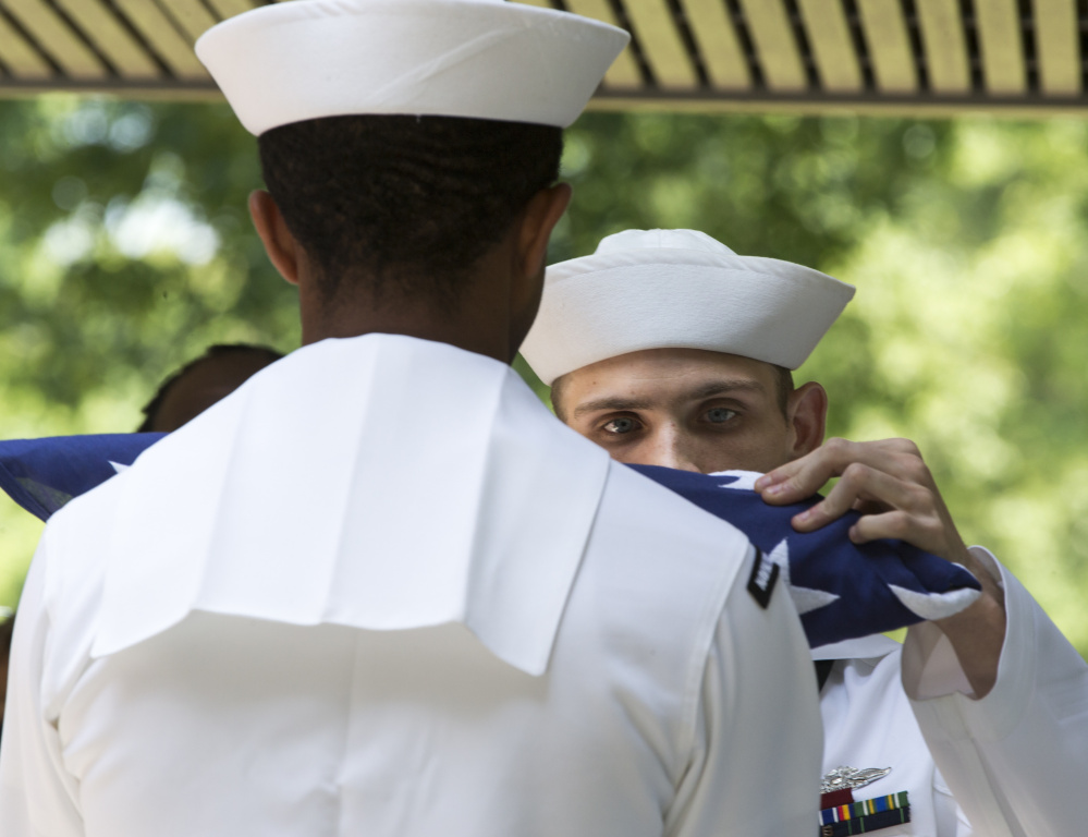 Petty Officer 2nd Class Dwight Merkle, right, prepares the ceremonial flag for presentation during the funeral  for World War II veteran Serina Vine
