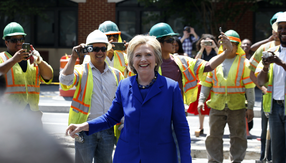Hillary Clinton is all smiles greeting workers after a stop at the Uprising Muffin Co. in Washington, D.C., on Friday, a day after securing President Obama's endorsement as well as that of Vice President Joe Biden and Sen. Elizabeth Warren.