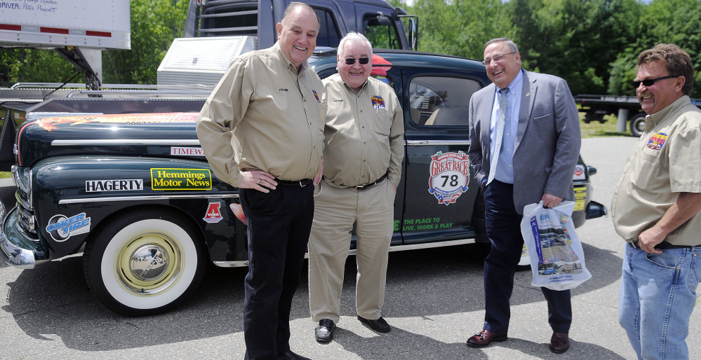 Race team members Frank Crooker, left, Peter Prescott and John Myrick, right, laugh with Gov. Paul LePage at the team's garage in Gardiner.