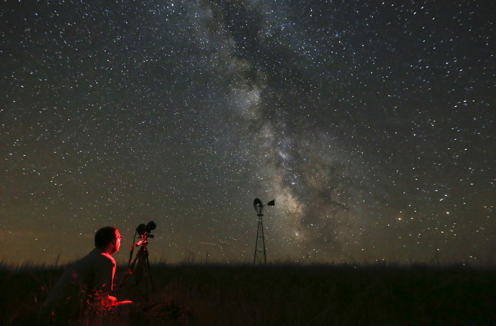 A man photographs the sky near Callaway, Neb., in July 2014, on a night when the Milky Way was visible to the naked eye. Light pollution obscures the Milky Way in much of the world.
