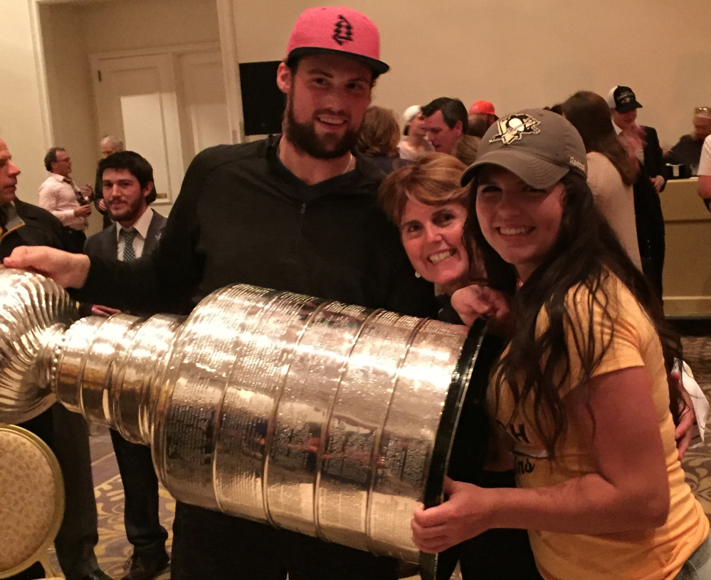 Brian Dumoulin celebrates with the Stanley Cup alongside his mother, Deborah, center, and his sister, Katherine. Dumoulin and the Penguins wrapped up the title Sunday.