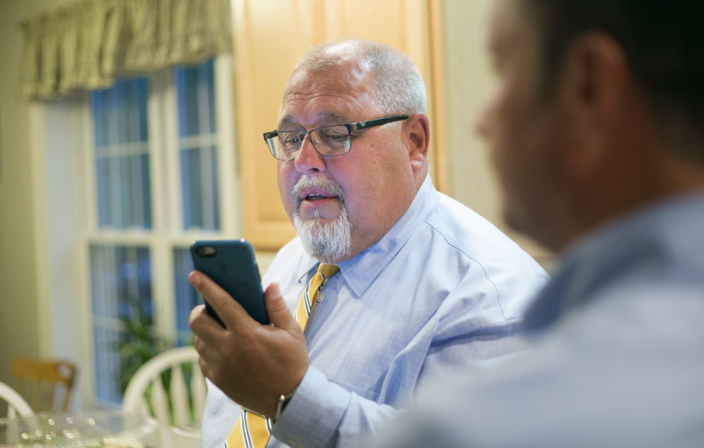 State Rep. Mark Dion checks for Senate District 28 election results on his phone Tuesday evening, accompanied by campaign manager Dennis Hersom, right. Derek Davis/Staff Photographer