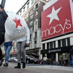 Shoppers carry bags as they cross a pedestrian walkway near Macy's in Herald Square in New York. Macy's said Thursday it has reached a tentative deal with the union representing workers at its flagship store in New York City.