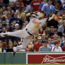 Orioles third baseman Paul Janish leaps to catch a sharp line drive by Boston's Xander Bogaerts in the seventh inning Thursday night at Fenway Park.