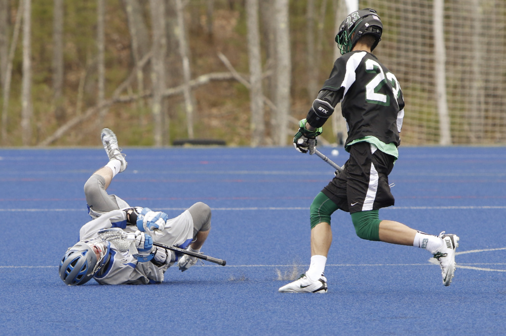 """University of New England's Mitch Mullin hits the turf under pressure from Anthony Verville of Nichols College during a lacrosse game in Biddeford. UNE is studying """"head hits"""" in the sport."""