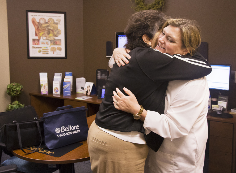 Pat Linhares, 75, of Old Orchard Beach, hugs specialist Karen Kirtani after being fitted for new hearing aids donated by Beltone in Scarborough.