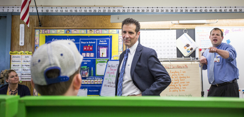 Xavier Botana, the new superintendent of Portland schools, visits a classroom at Hall Elementary School, engaging in a conversation about sports teams with a student, foreground, and assistant principal John Dickerson, far right.