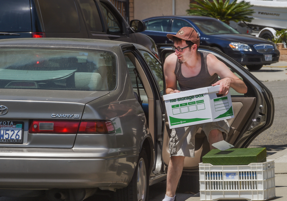 A resident of Duarte, Calif., a foothill city near Los Angeles, loads his car with possessions on Monday as he prepares to evacuate his home as a wildfire burns nearby.