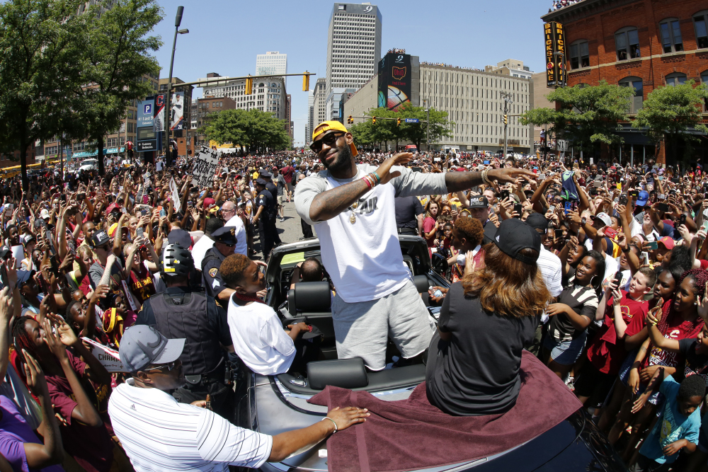 Cleveland Cavaliers' LeBron James stands in the back of a Rolls Royce as it makes its way through the crowd lining the parade route in downtown Cleveland on Wednesday, celebrating the basketball team's NBA championship.