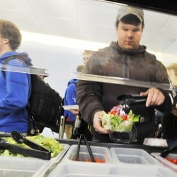 Senior Kenny Davis adds a tomato to his salad at Kennebunk High School's cafeteria in November 2014. Federal reforms implemented in 2012 have boosted U.S. K-12 students' fruit and vegetable consumption.