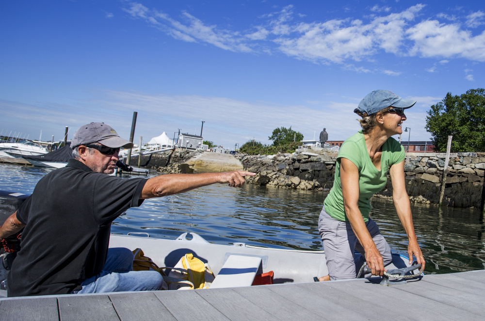 In their dinghy, Jack and Zdenka Griswold pull up to the dock at Portland Yacht Services on Wednesday morning, coming to the end of a seven-year adventure sailing around the world.